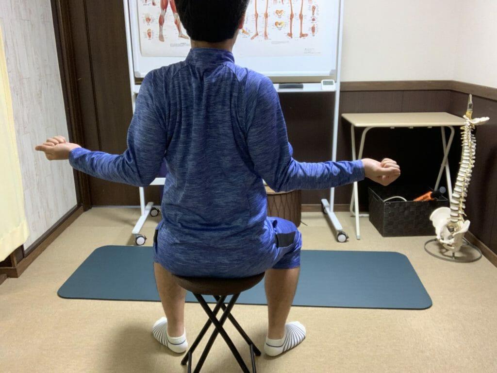 【肩こり解消ストレッチ】肩甲骨を寄せて胸筋を伸ばすストレッチを後方から見た様子