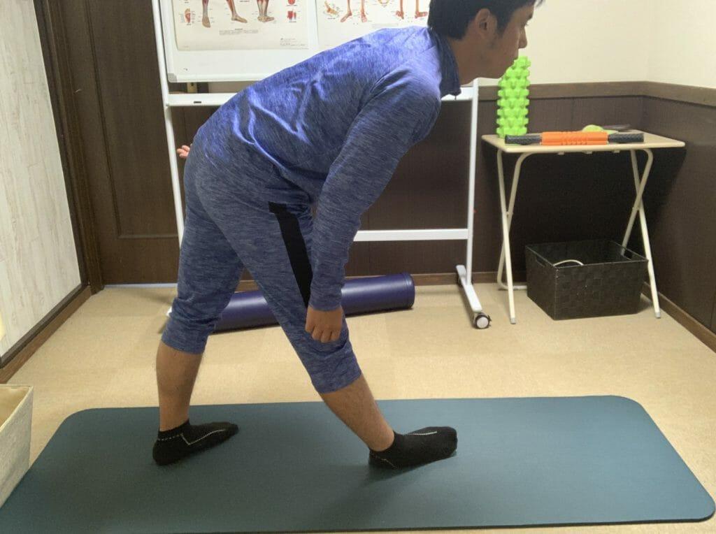 立って片方のすねの外側をストレッチするときは、骨盤を前に倒す